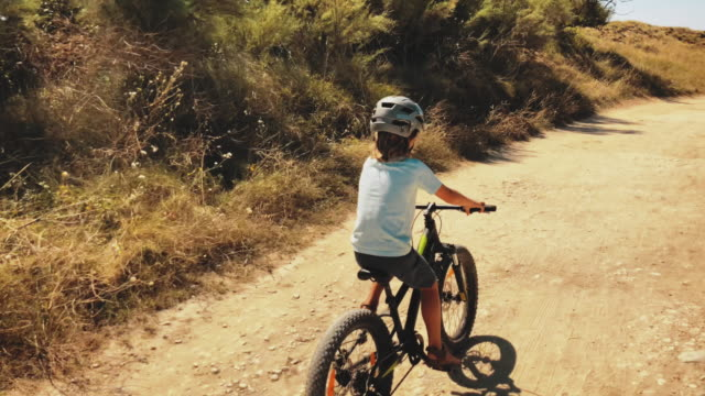 stockvideo's en b-roll-footage met boy riding fiets op dirt road tijdens de zomer - sporthelm