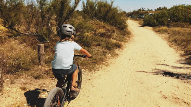 boy riding bicycle on dirt road - crash helmet stock videos & royalty-free footage