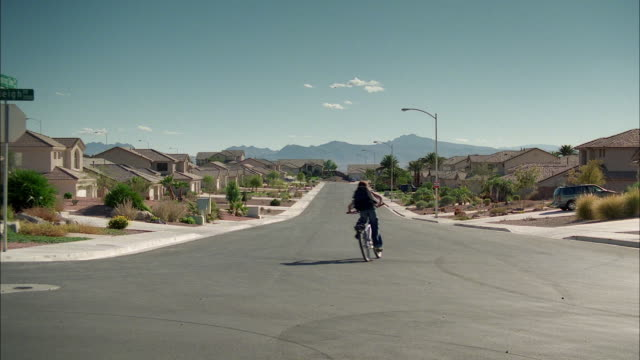 ws cs boy riding bike through town, with cityscape and distant mountains / las vegas, nevada, usa - nevada stock-videos und b-roll-filmmaterial