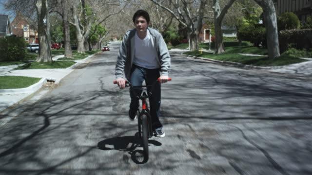 TS, MS, boy riding his bike down a street, front view