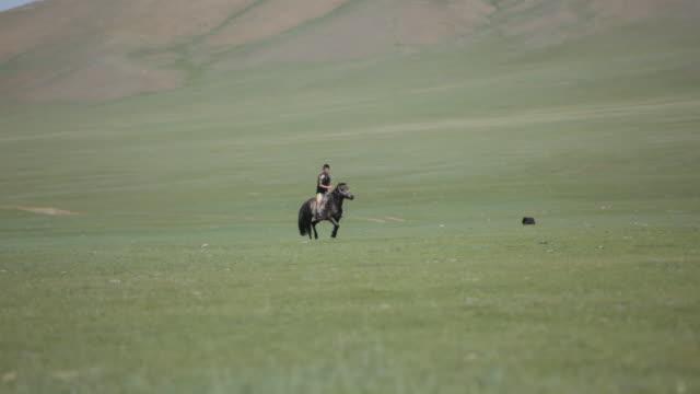 Boy riding horse through nomad camp
