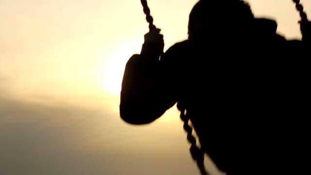 Junge auf einer Schaukel mit Sonnenuntergang