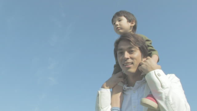 boy riding on fatehr's shoulders with blue sky in background - 肩に乗せる点の映像素材/bロール