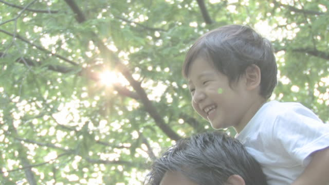 boy riding on father's shoulders - 肩に乗せる点の映像素材/bロール