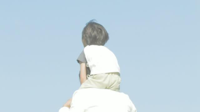 boy riding on father's shoulders - son点の映像素材/bロール