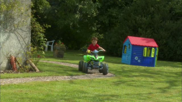 MS, CU, Boy (4-5) riding quad bike in garden, Brussels, Belgium