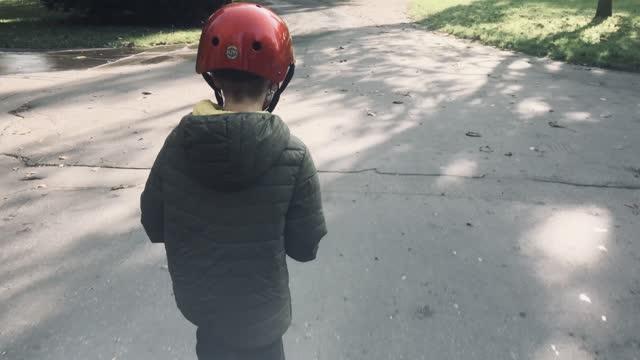 vídeos de stock, filmes e b-roll de menino andando de scooter no parque - atividade recreativa