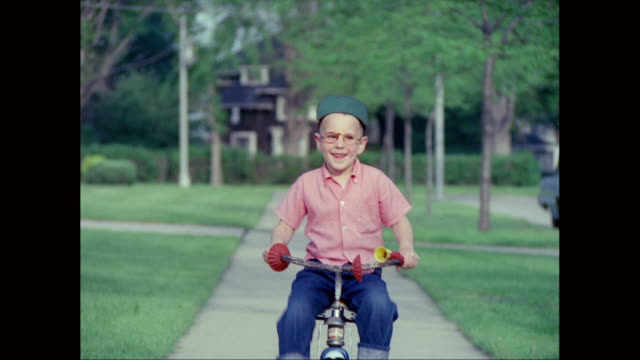 MS Boy riding tricycle on suburban sidewalk / United States