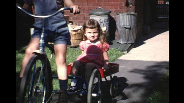 1953 montage boy (2-3) riding tricycle pulling girl in wagon, toronto, ontario, canada - tricycle stock videos and b-roll footage
