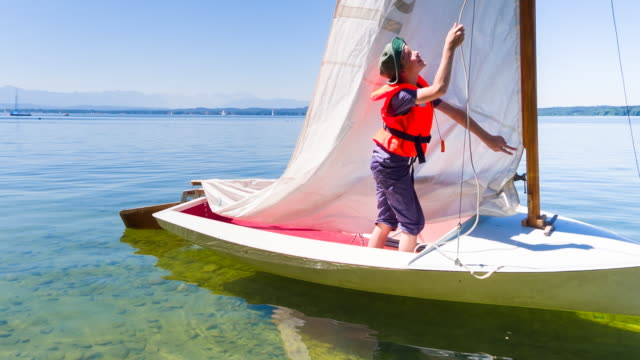 ms boy rigging sail on small sailboat - sailing boat stock videos & royalty-free footage