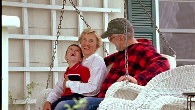 A boy rocks in a porch swing with his grandparents.