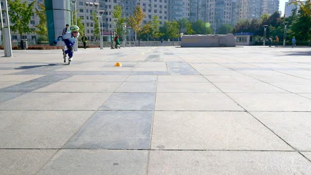 jongen rolschaatsen op marmeren plein in Peking