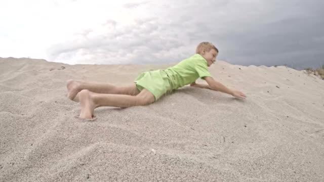 vídeos y material grabado en eventos de stock de niño rodando por una duna de arena - movimiento hacia abajo
