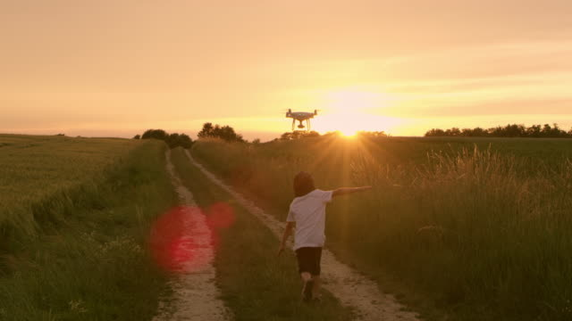 slo mo boy running after a drone - arms outstretched stock videos and b-roll footage