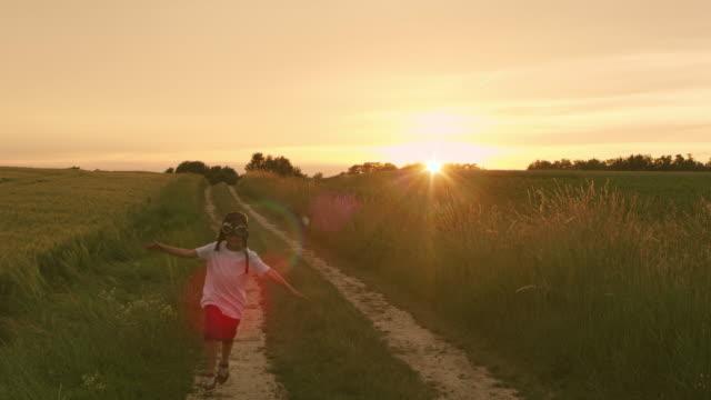 SLO MO Boy running among wheat fields at sunset