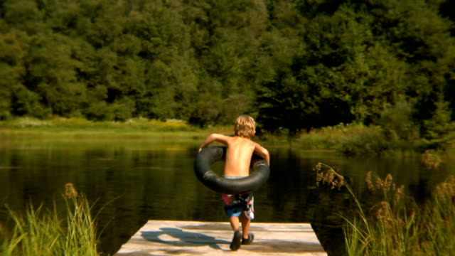 vídeos de stock e filmes b-roll de sm ws boy running and jumping off of pier into pond with inner tube/ bovina, new york - pequeno lago