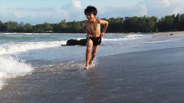 vidéos et rushes de garçon exécutant à la plage, ralenti - 8 9 ans
