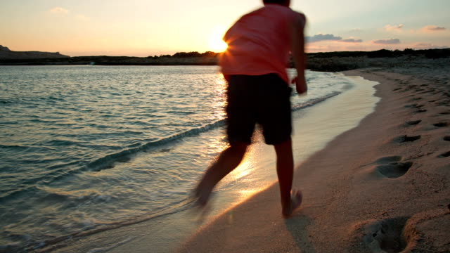 HD: Boy running at lonely beach at sunset