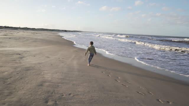 vídeos de stock e filmes b-roll de boy running at the beach - montevidéu
