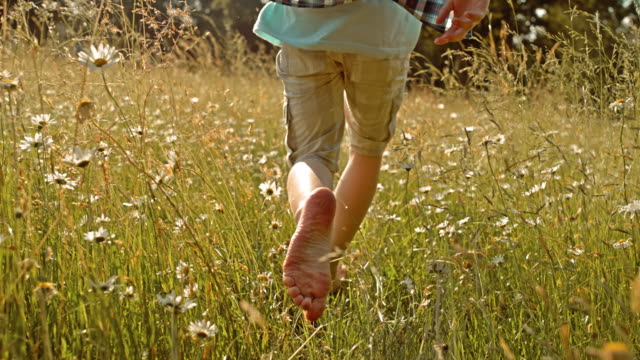 SLO MO TS Boy running barefoot in high grass