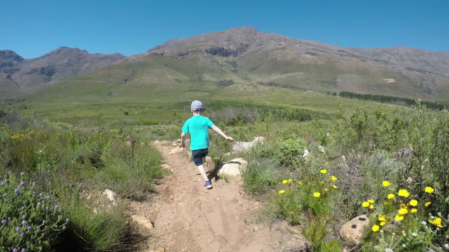 boy running down the mountain path - following moving activity stock videos and b-roll footage