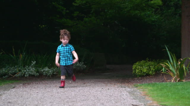 boy running in park - ein junge in gummistiefel stock-videos und b-roll-filmmaterial