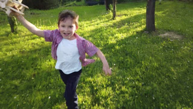 boy running in the backyard holding a wooden airplane - holing stock videos & royalty-free footage