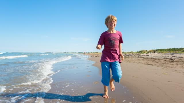 vidéos et rushes de ms boy running in the surf at adriatic beach - petits garçons