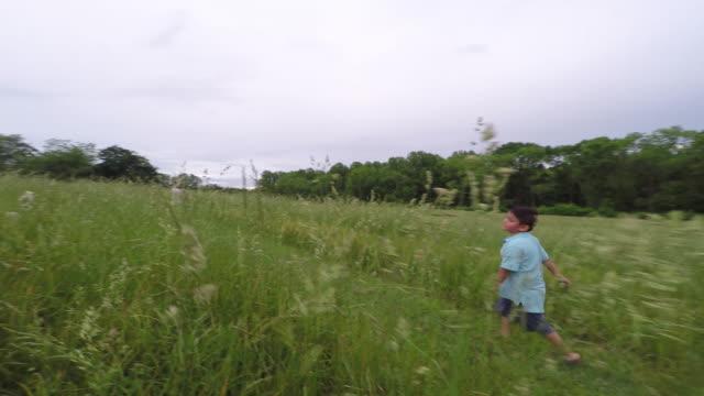vidéos et rushes de boy running on a grass trail path. - latin american culture