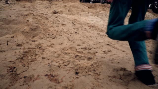 スローモーションで砂崖の上を走っている少年