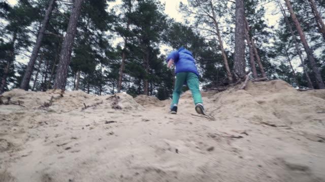 stockvideo's en b-roll-footage met jongen wordt uitgevoerd op een zanderige klif - menselijke rug