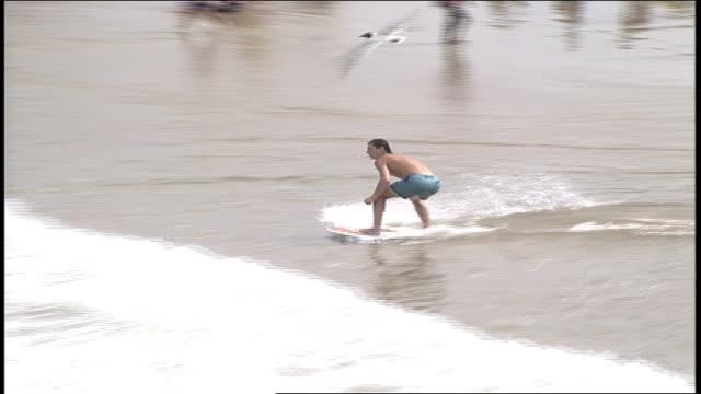 boy running then falling off boogie board at beach in virginia - virginia beach stock videos & royalty-free footage