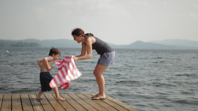MS Boy running to his mother and she wrap him with beach towel on dock / WOLFEBRO, NH, USA