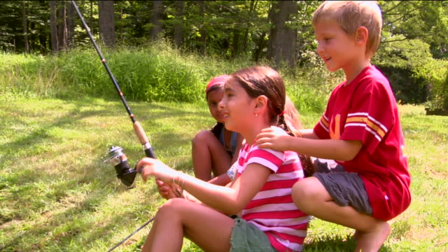 ms boy running up behind three girls sitting with fishing rods in grass / sherman, ct, usa - maschio con gruppo di femmine video stock e b–roll
