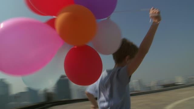 vídeos de stock, filmes e b-roll de ms pov boy running with balloons / bangkok, bangkok, thailand - bexiga