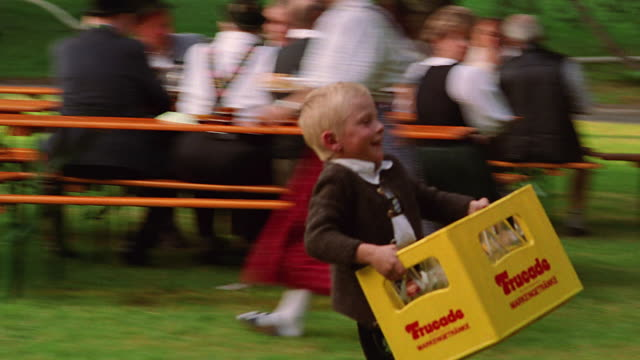 PAN boy running with case of beer in park / people at picnic tables in background / Bad Kohlgrub, Bavaria