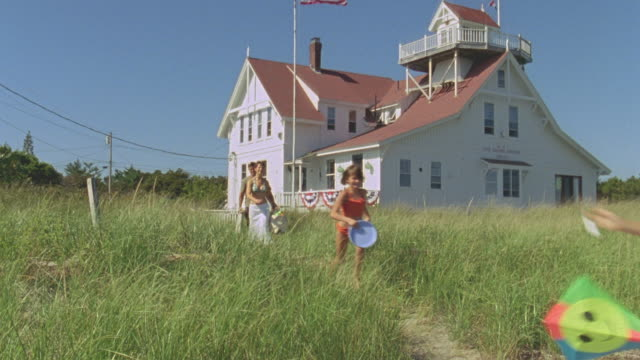 vídeos de stock, filmes e b-roll de ws boy running with kite along beach path near inn with family following / phippsburg, maine, usa  - pipa brinquedo