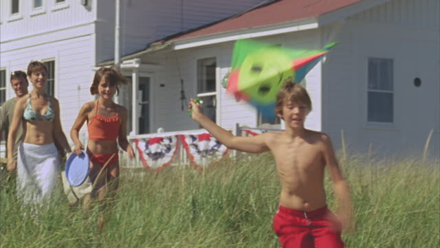 ms boy running with kite along beach path near inn with family following / phippsburg, maine - オオハマガヤ属点の映像素材/bロール