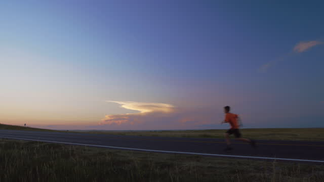boy runs alone across empty highway with open sky and endless grass prairie stretching into the distance. - badlands national park stock videos & royalty-free footage