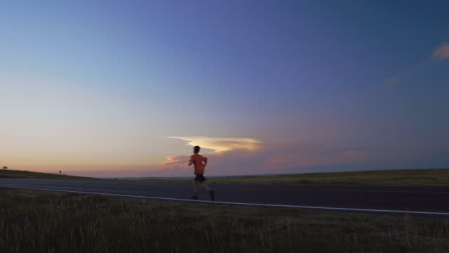 boy runs alone across long empty road with open sky and endless grass prairie landscape stretching into the distance. - badlands national park stock videos & royalty-free footage