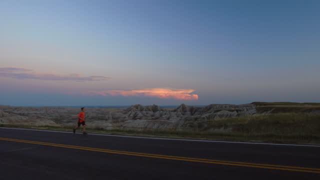 boy runs alone down empty highway overlooking the badlands of south dakota at sunset. - バッドランズ国立公園点の映像素材/bロール