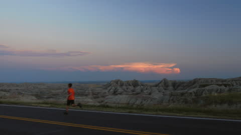 boy runs alone on long empty road overlooking the rugged and beautiful badlands landscape at sunset. - badlands stock videos & royalty-free footage