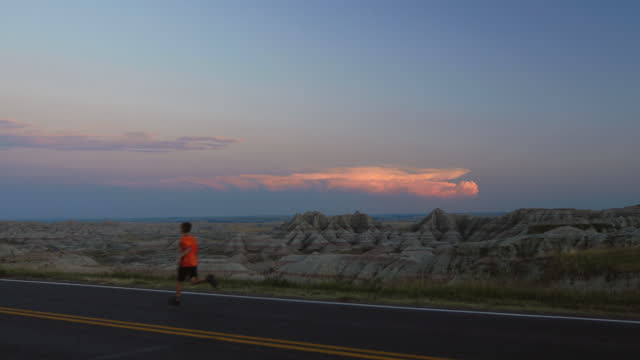 boy runs alone on long empty road overlooking the rugged and beautiful badlands landscape at sunset. - badlands national park video stock e b–roll