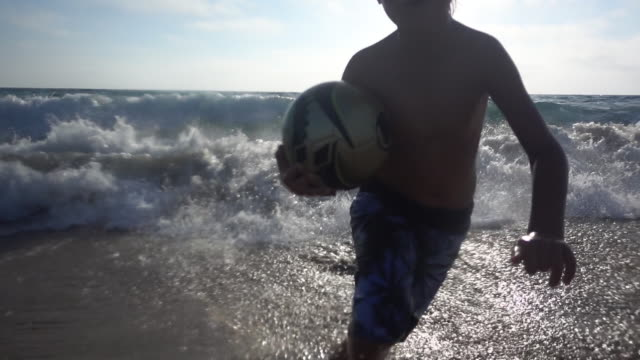 A boy runs from the waves with a soccer ball at the beach.