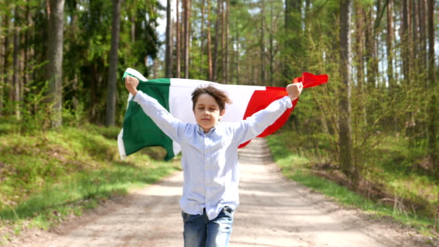 a boy runs through the woods with the flag of italy - flag video stock e b–roll