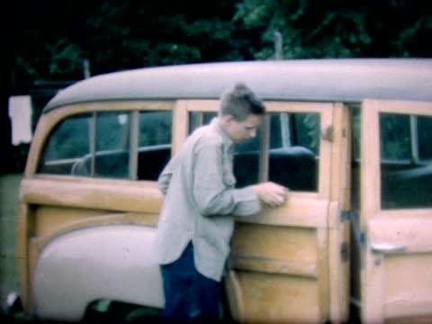vídeos y material grabado en eventos de stock de 1947 boy sanding wood-paneled station wagon - un solo adolescente
