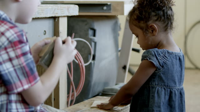 Boy sands a wood panel piece while young girl plays in the wood shop.