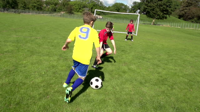 Boy scoring goal in Kid's football / Soccer Match