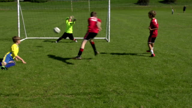 boy scoring goal in kid's soccer / football match - scoring a goal stock videos and b-roll footage