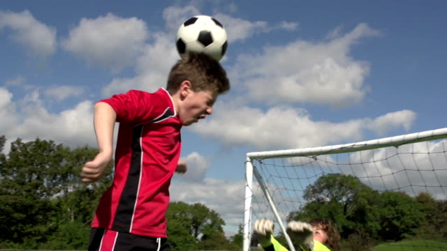 boy scoring soccer goal with header - kid's football - scoring a goal stock videos and b-roll footage